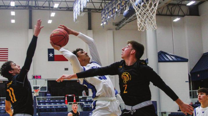 Fort Stockton's Ethan Acosta attacks the basket near the start of Tuesday's game in Fort Stockton while Seminole's River Powers (11) attempts to block the shot from behind. Photo by Nathan Heuer