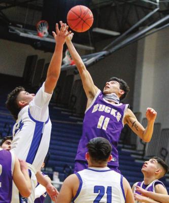 Fort Stockton sophomore Cruz Rojas, left, skies for a rebound against Alpine's Isaiah Nunez (11) during Friday's game at the Special Event Center. Photo by Nathan Heuer